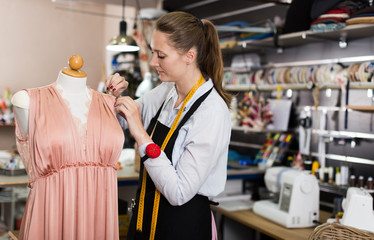 Woman worker measuring new dress at  mannequin at atelier