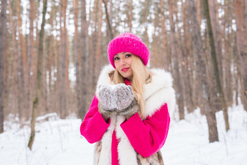 Fashion, nature, people concept - beautiful blond woman holding snow in her hands
