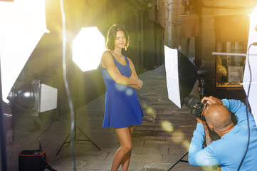 Professional photo shooting outdoors. Attractive female model po