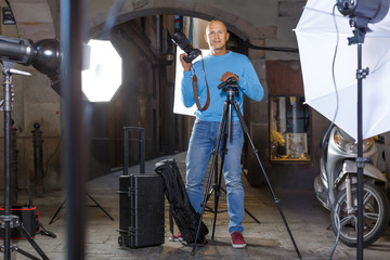 Professional glad photographer  holding camera
