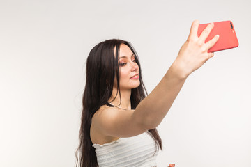 Happy european female model with dark hair enjoying indoor photoshoot. Young woman is taking a selfie on light background