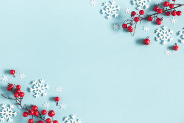 Christmas or winter composition. Frame made of snowflakes and red berries on pastel blue background. Christmas, winter, new year concept. Flat lay, top view, copy space Fotoväggar