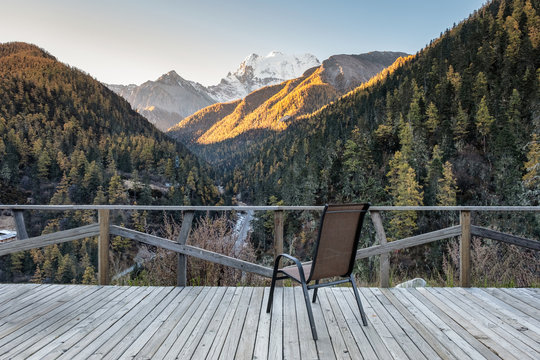 Chair on wooden balcony with valley in autumn at evening