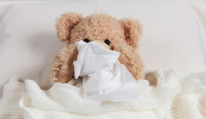 Cold, flue or allergy. Cute teddy in bed, covered with a warm blanket, holding a tissue
