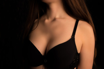 Beautiful woman's breasts in bra on black background