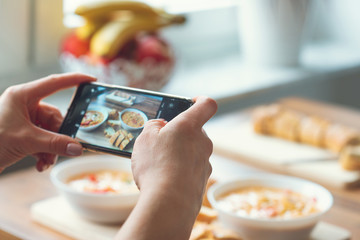 Closeup how woman taking photo of vegetarian food at home