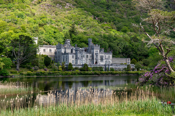 Landscape with a beautiful lake and castle reflected in the water on a summer day.  Kylemore Abbey in Connemara, County Galway, Ireland.