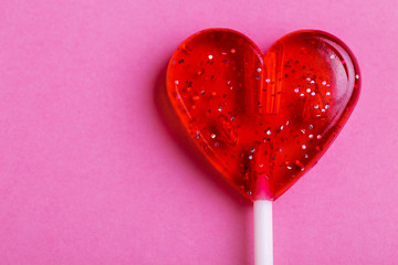 Red sweet tasty lollipop in shape of heart