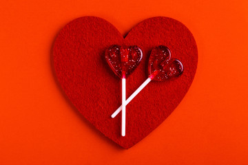 Two red sweet tasty lollipops and felt heart
