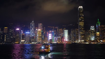 Fototapete - Skyscrapers and floating ship at Victoria's harbor, Hong Kong at night. 4K