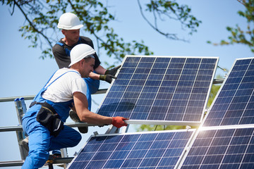 Two workers mounting heavy solar photo voltaic panel on tall steel platform on blue sky background. Exterior stand-alone solar panel system installation, dangerous job concept.