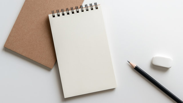 open blank spiral notebook with pencil and eraser on white background.Empty Space for your text.