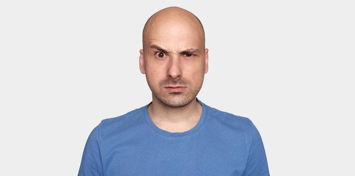 man raised his eyebrow. Angry bald guy isolated