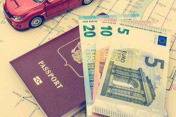The concept of car travel: the passport and map. A few bills-Euro cash. Red car model. Soft processing in retro style