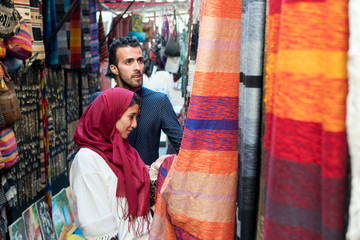 Smiling young muslim couple shopping carpets in a textile store