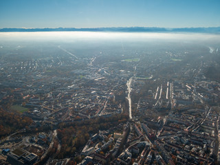 Helicopter view to Munich Region with autumn fog and long view to alps