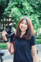 Beautiful and Happy Asian Woman holding Camera in the Garden.