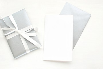 Greeting card mock up template to place your design. Blank white card, silver envelope, gift box, top view.