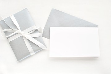 Empty card and envelope, gift box with ribbon, modern white and silver flat lay,  greeting card mock up.
