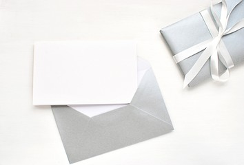 Modern flat lay with blank card and silver envelope, Christmas, New Years, wedding greeting card, invitation mock up.