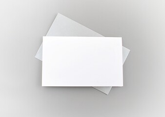 White greeting card and silver envelope on gray background to place your design.