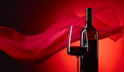 Glass and bottle of red wine on a red background.