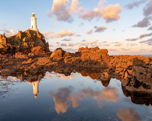 Coastal reflections at Corbiere, Jersey, Channel Islands lit by warm morning sun