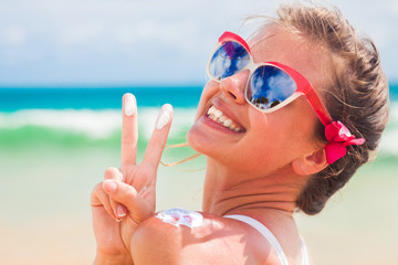 Close up of young woman in sunglasses putting sun cream on shoulder