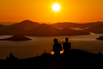 silhouettes of a couple at the romantic sunset on the island