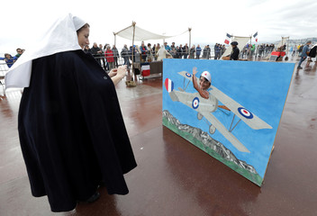 A World War One Historical Association member dressed as nurse takes a photo during the centenary anniversary of the WW1 Armistice Day in Nice