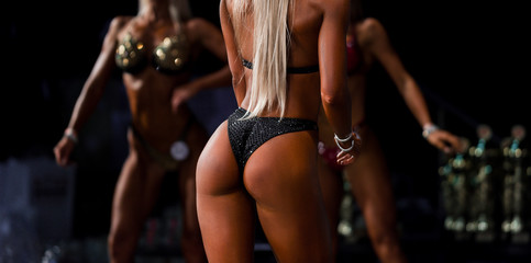 Sexy butt in black bikini. Fitness bikini girl on stage. Beautiful tanned female bodies.