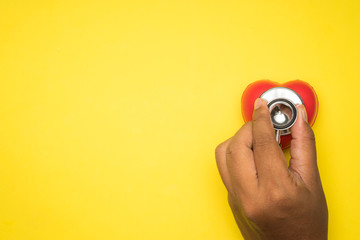 Healthcare or medical concept. Stethoscope and a red heart on a yellow background. Flat lay or top view. Wall mural