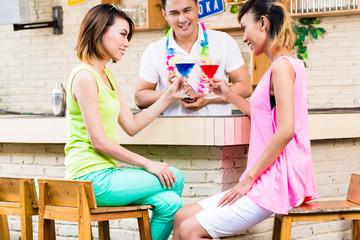 Two pretty women sitting at bar counter holding red and blue cocktail in front of bartender