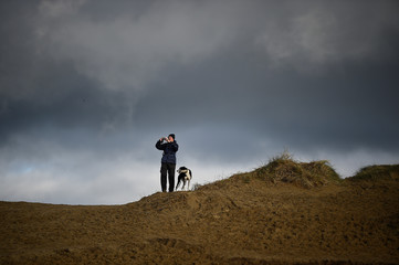 A man takes a picture from a hilltop as volunteers draw depictions of those killed in World War One, as part of Danny Boyle's Pages of The Sea celebrations, on Murlough Beach in Newcastle