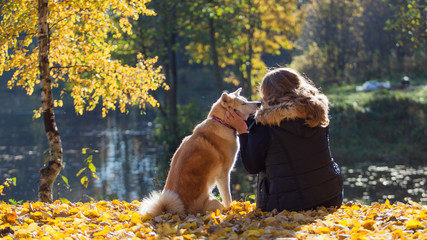 Young woman on a walk with her dog breed Akita inu