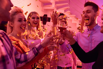 Group of young people clinking with champagne in flying golden confetti having New Year party