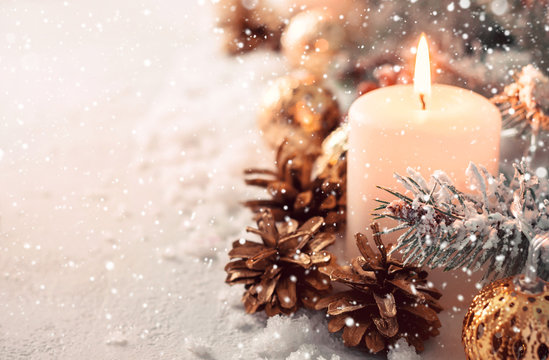 Beige snow Christmas composition. Burning candle and fir cones