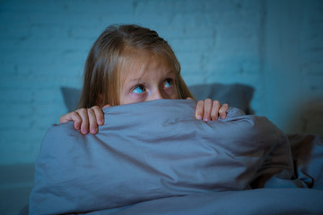 Sleepless cute girl in fear at night hiding behind the blanket afraid of dark and monsters
