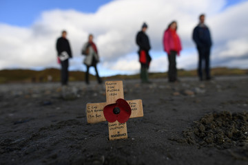 A remembrance cross is planted in the sand as volunteers draw depictions of those killed in World War One, part of Danny Boyle's Pages of The Sea celebrations, on Murlough Beach in Newcastle