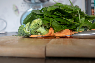 Fresh Spinach, broccoli and sweet potatoes on a chopping board.