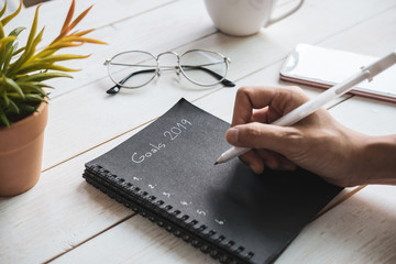 2019 goals text on notebook with smartphone on white wooden desk, Top view