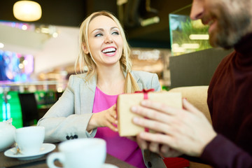 Portrait of adult couple exchanging presents at table in cafe, focus on happy woman holding gift box