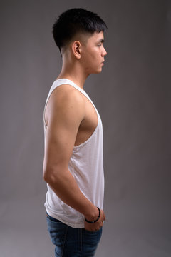 Young handsome Asian man wearing tank top against gray backgroun