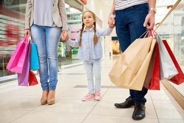 Portrait of happy family shopping in mall, focus on cute little girl holding hands with parents