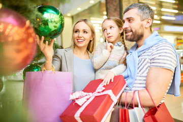 Couple with little daughter looking at baubles on Christmas tree while shopping together