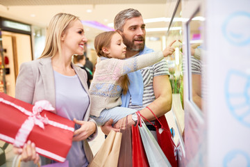 Side view of adult parents with little girl carrying paper bags having Christmas shopping and exploring shop window