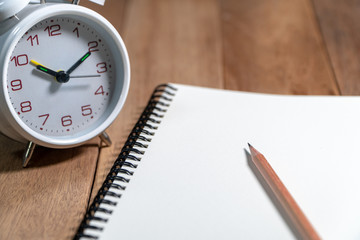Wooden pencil placed on the empty notebook with white vintage alarm clock on the wooden table. Copy space for add text.