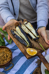Woman hands holds roasted, grilled, baked eggplants on wooden cutting board. Vegan vegetarian healthy food, paleo diet. Vegetables