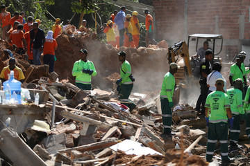 Rescue workers remove debris at the site of a landslide at the Boa Esperanca slum in Niteroi