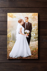 Photo of a wedding couple printed on canvas. Photography with stretch on a wooden frame on a brown wall background